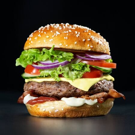Burger frais et savoureux sur fond sombre Banque d'images