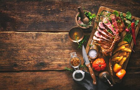 Grilled meat, sliced tomahawk beef steak with spices, french fries and vegetables on a rustic background Imagens