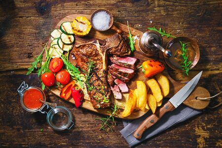 Beef steak with grilled vegetables and seasoning on serving board
