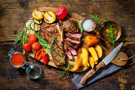 Beef steak with grilled vegetables and seasoning on serving board Stock Photo