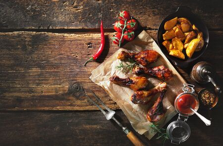 Grilled chicken drumstick served on paper with french fries and sauce, close up view on rustic wooden table