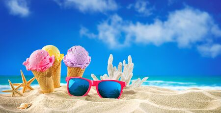 Ice creams cones and seashells in the sand on the beach with ocean landscape Imagens