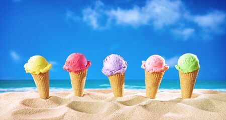 Ice creams cones and seashells in the sand on the beach with ocean landscape