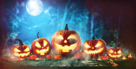 Halloween pumpkin head jack-o-lantern in front of a spooky forest