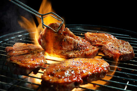 Marinated pork steaks on barbecue grill with flames