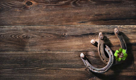 Two old rusty horse shoes and four leaf clover as symbol for lucky charm on a rustic wooden background Reklamní fotografie