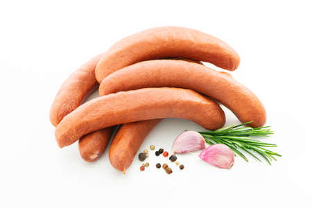 Raw meat sausages garnished with pepper, garlic and herbs. Isolated on white background