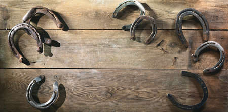 Old rusty horse shoes lying on a wooden barn floor Archivio Fotografico