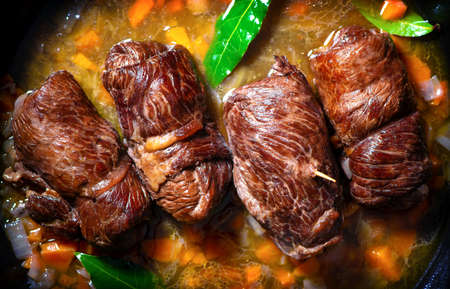 Traditional german meal of beef roulades in roast pot with fresh vegetables and seasoning on a kitchen table