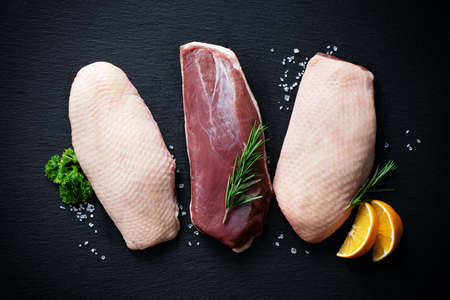 Raw duck breast pieces garnished with rosemary and orange slices on dark slate background