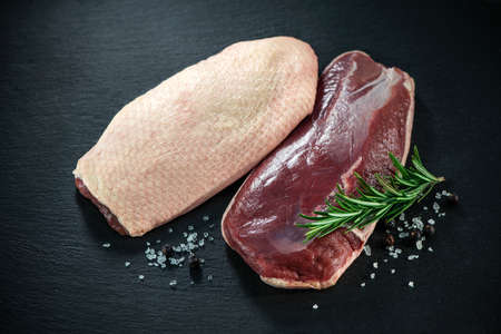 Raw duck breast pieces garnished with rosemary on dark slate background