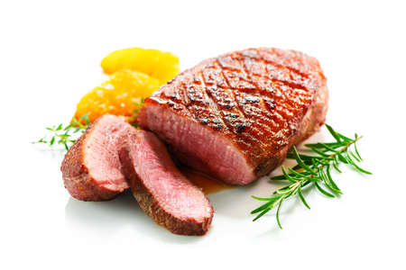 Close up of roasted duck breast fillet garnished with rosemary and spices isolated on white Reklamní fotografie