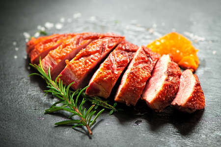 Close up of sliced roasted duck breast fillet garnished with rosemary and spices on slate