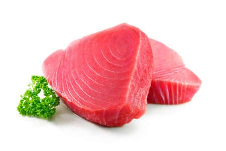 Fresh tuna fish fillet steaks garnished with parsley isolated on white background