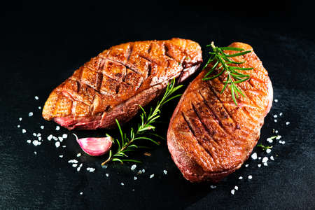 Close up of roasted duck breast fillet garnished with rosemary and spices on slate