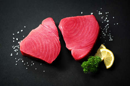 Fresh tuna fish fillet steaks garnished with parsley and lemon slices on dark background