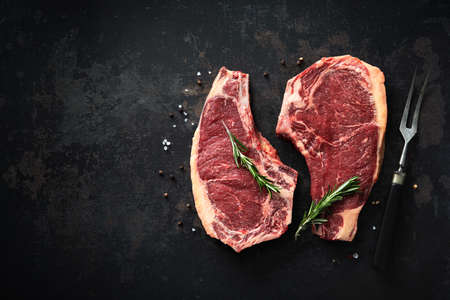 Two raw dry aged beef rib steaks (cote de boeuf)  with rosemary, pepper and salt on dark background Reklamní fotografie
