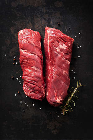 Two raw hanger steaks, also known as butchers steak or hanging tenderloin with rosemary, pepper and salt on dark background