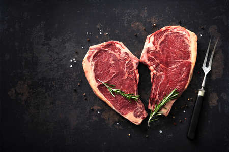 Heart shape raw dry aged beef rib steaks (cote de boeuf) with rosemary, pepper and salt on dark background