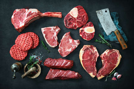 Variety of raw cuts of meat, dry aged beef steaks and hamburger patties for grilling with seasoning and utensils on dark rustic board