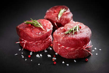 Raw beef filet mignon steaks with rosemary, pepper and salt on dark rustic board, black angus meat Reklamní fotografie
