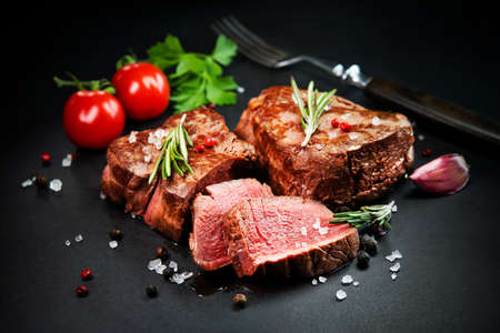 Grilled beef filet steaks with herbs and spices on dark slate background Reklamní fotografie