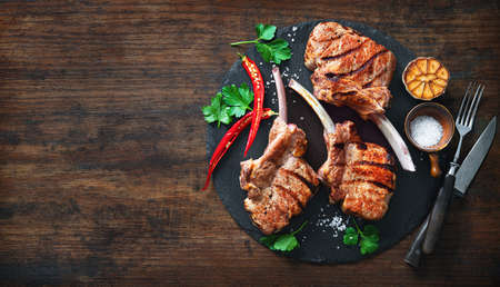Grilled veal meat ribs cutlets with ingredients on wooden table, top view. Frenched Racks meat Reklamní fotografie