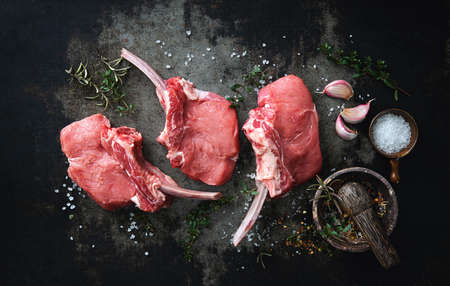 Raw veal meat ribs cutlets with ingredients on rustic dark background, top view. Frenched Racks meat