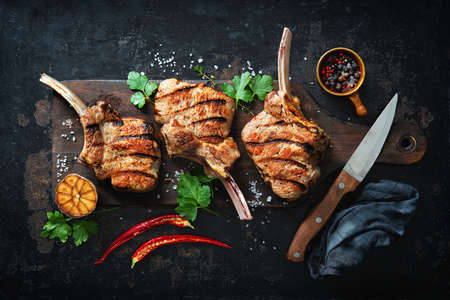 Grilled veal meat ribs cutlets with ingredients on rustic dark background, top view. Frenched Racks meat Reklamní fotografie