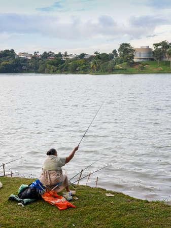 Women fishing on polluted lake in Pampulha, Belo Horizonte, Brazil Editorial