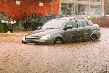 Unidentifiable passengers stuck in a car during heavy rains and flash flood - insurance claim concept