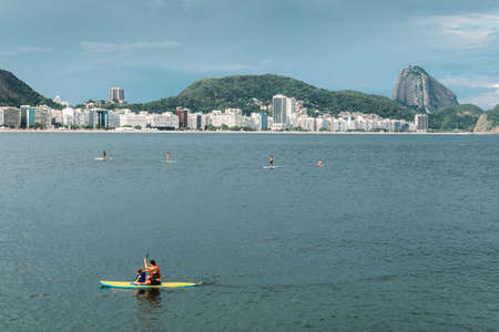 Rio de Janeiro, Brazil - January 3rd, 2018: Father and daughter Stand Up Paddle on Copacabana Beach