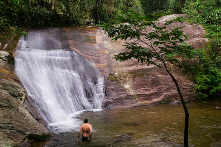 Unidentifiable man relaxing at waterfall in tropical rainforest