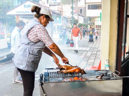 Ecuadorian woman preparing an Ecuadorian delicacy called lechon , bbq a small type of pig on grill