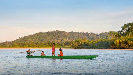 Les adolescents locaux de la tribu Quechua en Amazonie équatorienne sur un canoë sur la rivière Napo