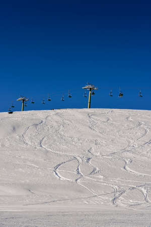 Winding snowboard trace and chairlift shadow on white snow - winter sports concept Фото со стока