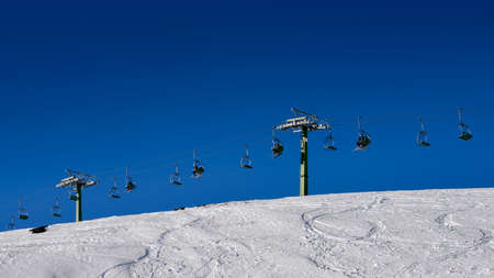 Winding snowboard trace and chairlift shadow on white snow - winter sports concept Stock Photo