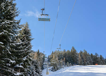 Chairlift at Italian ski area on snow covered Alps and pine trees during the winter - winter sports concept Фото со стока