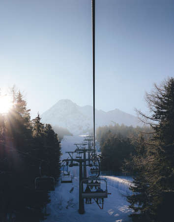 Sun through pine trees as chairlift ascent at Italian ski area covered in snow  - winter sports concept