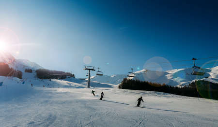 Unidentifiable skiers at ski resort in Pila, Valle d'Aosta, Italy with chairlift and mountain backdrop and copy space - winter sports concept 스톡 콘텐츠