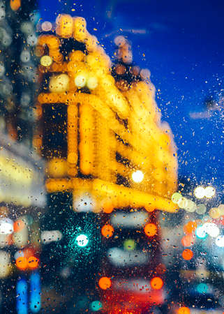Emotional melancholic abstract background with defocused lights bokeh in London, UK behind rain drops in window glass - Focus on few drops due to the shallow depth of field Stock Photo