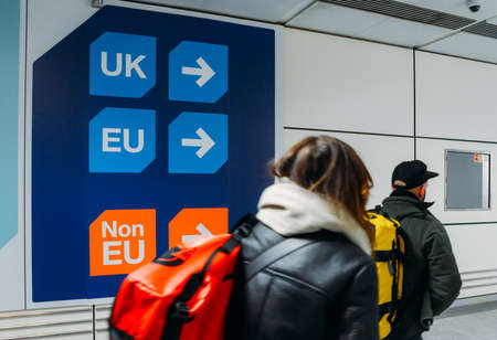 Passengers walks past sign prior to immigration control pass a si