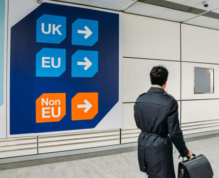 Passenger walks past sign prior to immigration control pass a sign pointing towards queues for UK, EU and Non-EU passport holders. In April 2019, UK is set to leave the European Union - Brexit theme