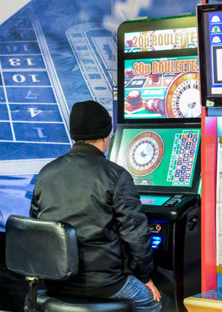 London, UK - Mar 5, 2018: Mature man using fixed odds Roulette machine in Bookmakers. London, England, UK. Machine described as the Crack Cocaine of Gambling and the maximum stake is set to be GBP 2 Editorial