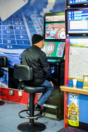 Mature man using fixed odds Roulette machine in Bookmakers. London, England, UK. Machine described as the Crack Cocaine of Gambling and the maximum stake is set to be GBP 2 Editorial