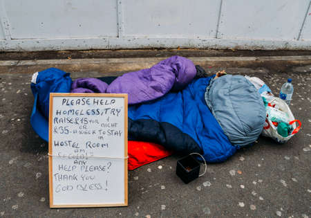 Sign on side of sidewalk of homeless person with sleeping bag, food and cup for change - austerity concept, captured in London, UK