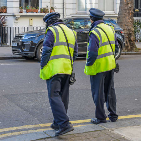 Two Highways Agency Traffic Officers, their purpose is to write tickets parking violations on Kensington and Chelsea, London streets Editoriali