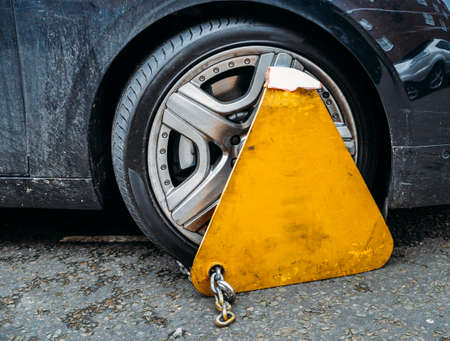 Yellow triangle wheel clamp locked with messing lock and chain on an illegally parked car Stock Photo