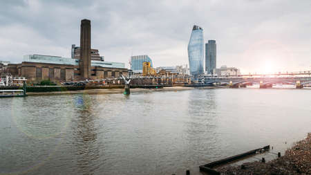 View from the northern side of the Thames towards unidentifiable pedestrians crossing the Millennium Bridge leading to Tate Modern - London, England, UK Stock Photo