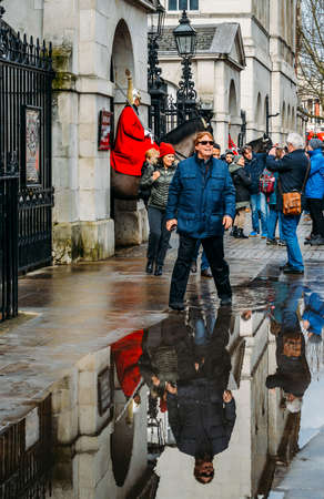 Horse Guard outside the Household Cavalry Division in Whitehall surrounded by tourists on a cold day Editorial